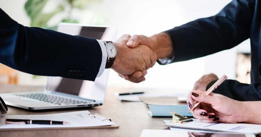 two people shaking hand in a meeting (featured image)